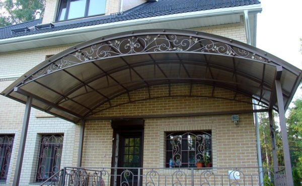 Фермическую конструкцию навеса можно декорировать ажурной художественной ковкой.