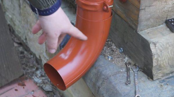 Между сливным коленом и отделкой цоколя оставляем небольшой зазор