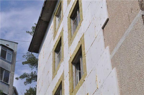 Пенопласт на фасаде многоэтажного дома.