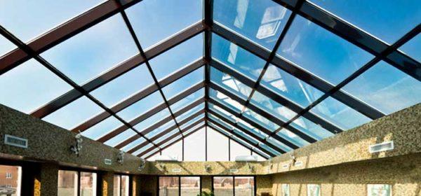 Сплошная двускатная конструкция из стекла и металла — хорошее решение для обустройства бассейнов, зимних садов и теплиц