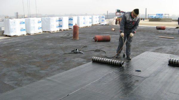 Укладка рубероида по крыше многоквартирного дома может выполняться прямо на старый рубероид